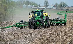 tractor pulls planter through field