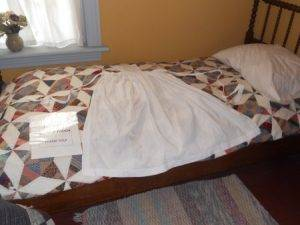 apron and quilt displayed on a bed