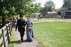 historic interpreters and visitors walk through town