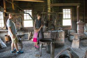 girl using bellows in blacksmith shop