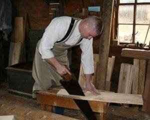 cabinetmaker saws through wood