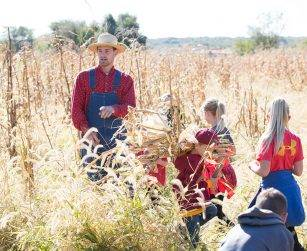 visitors help carry corn stalks as interpreter speaks