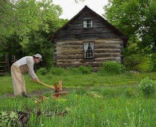 historic interpreter splits wood in front of log house