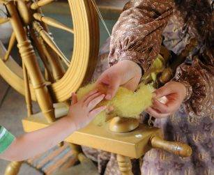 visitor feels wool as staff member puts it on spinning wheel
