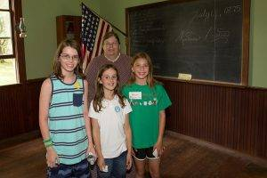 students pose with LHF staff member in the one room schoolhouse