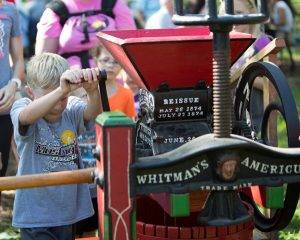 boy cranks cider press at applefest