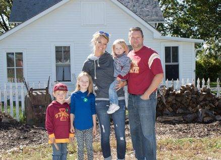 family poses in front of 1900 farm house