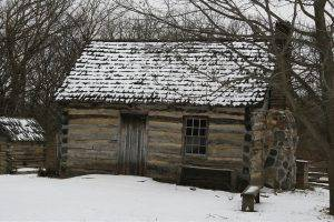 1850 log house in winter, covered by snow