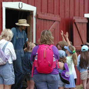 children interact with farmer in front of red barn
