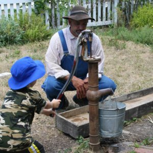 boy uses water pump as farmer looks on