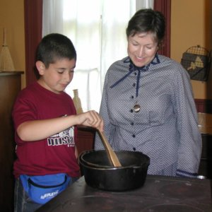 boy stirs pot on stove while historic interpreter looks on