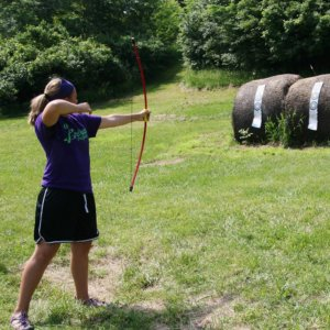 girl draws her bow and arrow, prepared to shoot a target