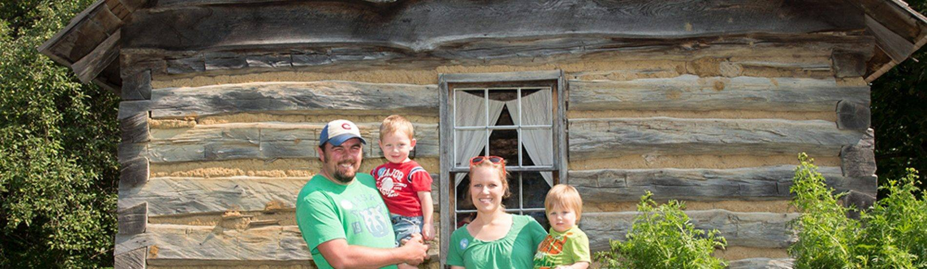 a family poses in front of the 1850 log house