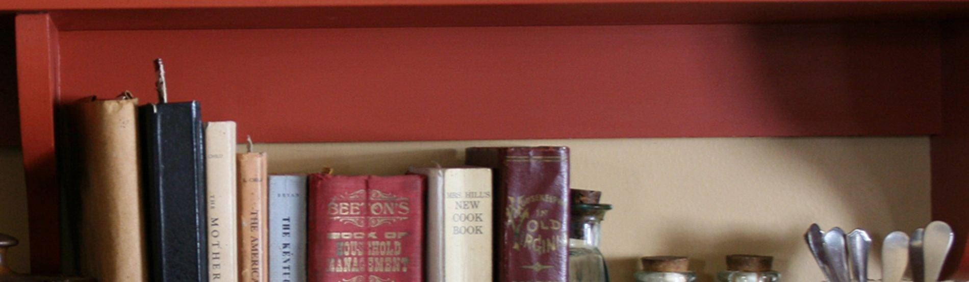 cookbooks and ingredients on kitchen shelf