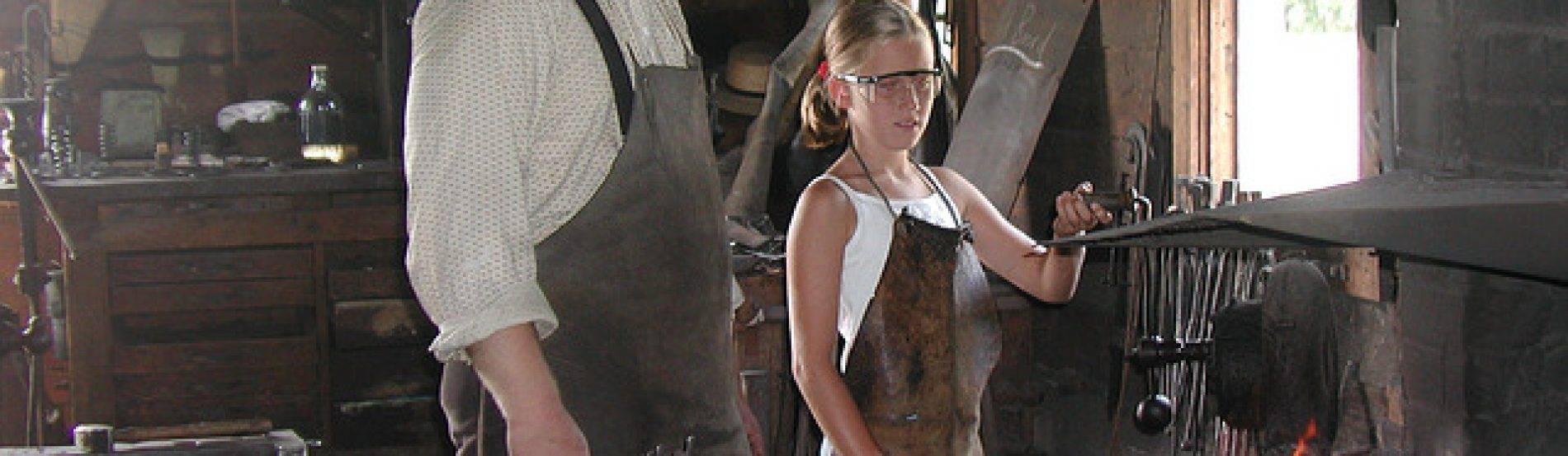 teen and LHF staff member work in blacksmith shop