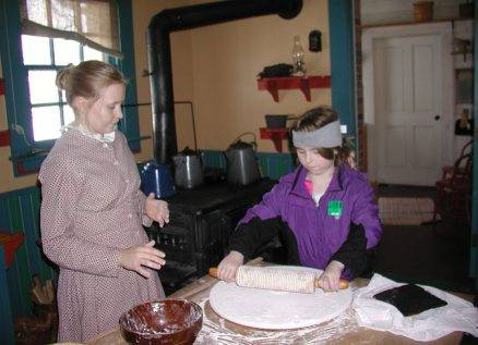 child rolls out dough for cookies in Tangen kitchen
