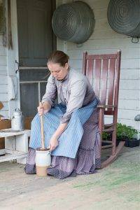 LHF staff member demonstrates butter churning on 1900 farmhouse porch