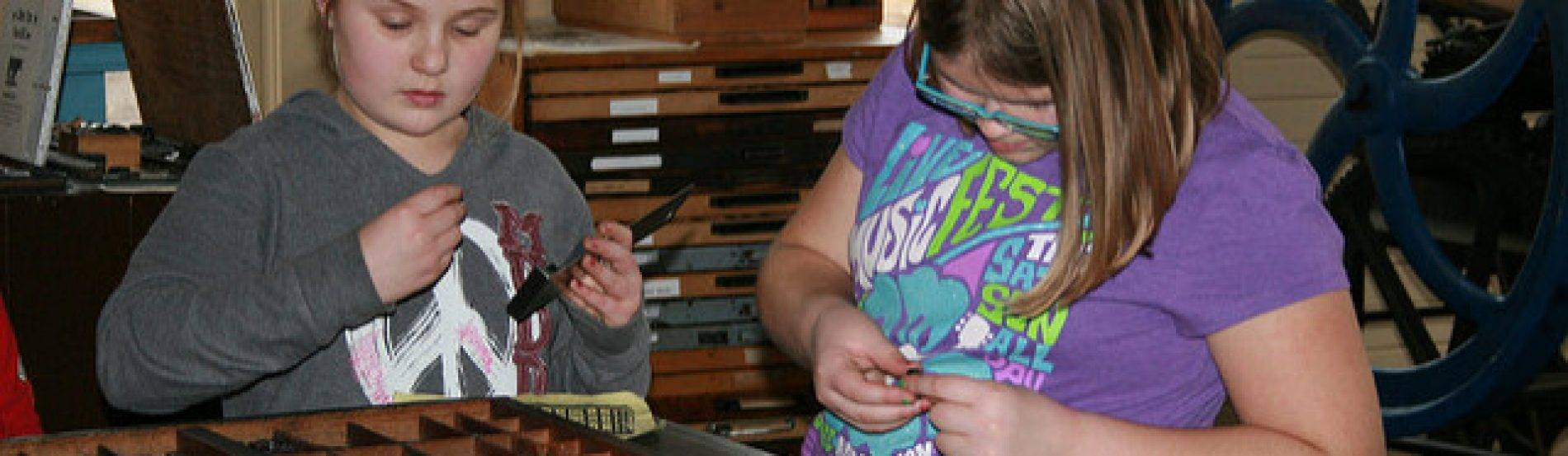 girls choose type for their projects in the print shop