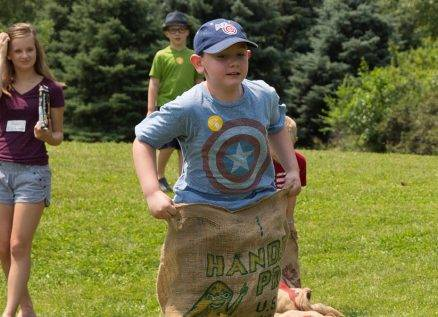 kids participate in sack race at independence day event