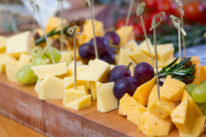 Snacks cheese and grape on the wooden board