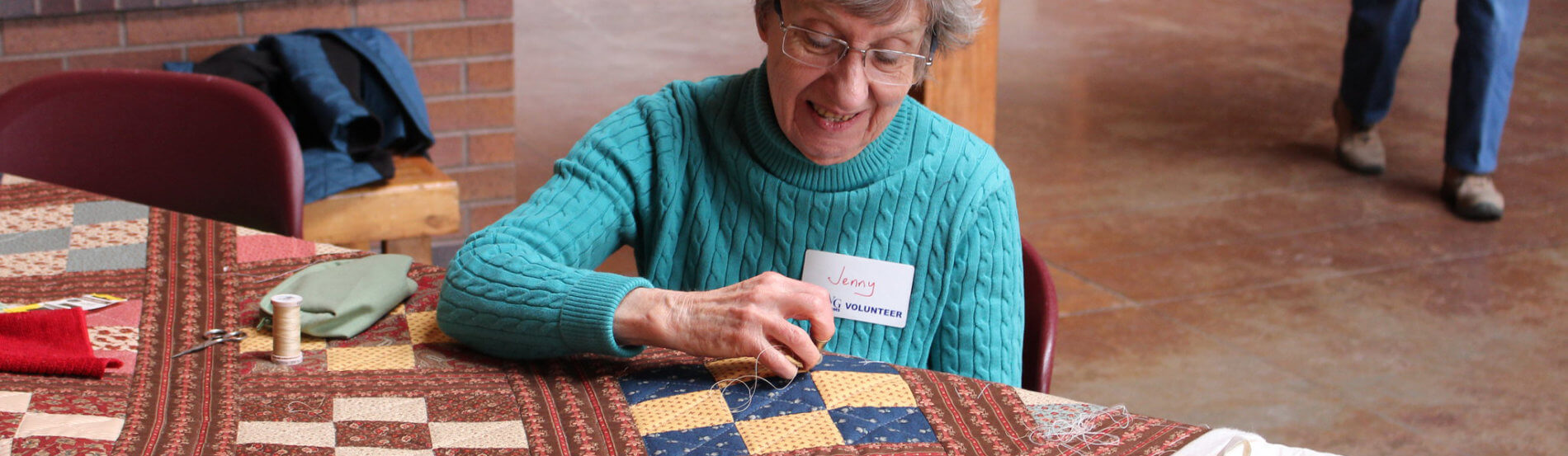 volunteer demonstrating quilting