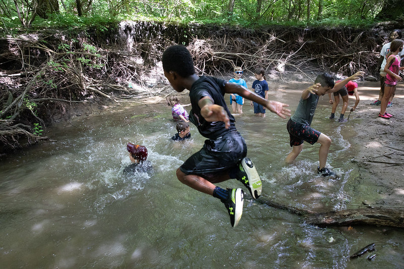 camp kid jumping in the creek