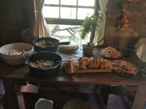 Food laid out on a table in 1850 cabin.